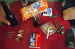 cluttered table top with unhealthful items, junk food, cigarettes, beer