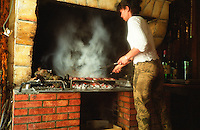 A woman making duck breast (magret de canard) on a grill barbeque bbq in a restaurant in Sauternes called Auberge les Vignes. Glowing coals and smoke, woman blurry blurred. real wood fire made with old vines, Sauternes, Bordeaux Gironde Aquitaine France Europe