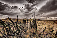 An old corral in the Rio Puerco Valley under a stormy sky with Cabezon Peak in the distance.