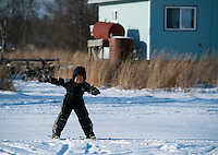 Bernard from Zackar Levi School in Lower Kalskag takes his first steps on skis in front of his school. Skiku is a non-profit organization with the mission of creating a sustainable Nordic ski program in communities throughout Alaska. Volunteer coaches travel to villages each spring to instruct youngsters and distribute donated equipment with the goal of establishing ski programs at rural schools.  Photo by James R. Evans