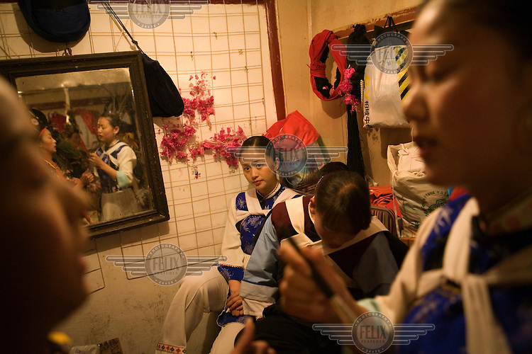 Performers in the changing rooms of the Dongba Palace, where a nightly show for tourists illustrates an important aspect of Nakhi (Naxi) culture. Dongba religion is a form of shamanism, and a Dongba shaman is a witch doctor, scholar, craftsman and artist, charged with disseminating Dongba culture. There are now very few Dongba shamans, as many of the younger generation have no interest in following this tradition.