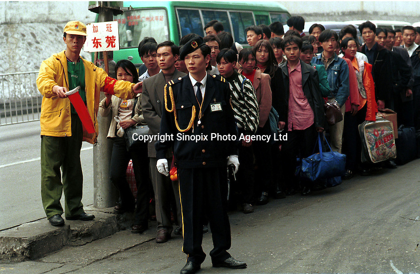 Local officials direct a group of migrants just arrived from northern China outside Guangzhou railway station. .06-MAR-99