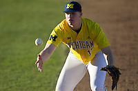 Michigan Wolverines first baseman Kendall Patrick (15) softly tosses the ball to the pitcher covering first base during the NCAA season opening baseball game against the Texas State Bobcats on February 14, 2014 at Bobcat Ballpark in San Marcos, Texas. Texas State defeated Michigan 8-7 in 10 innings. (Andrew Woolley/Four Seam Images)