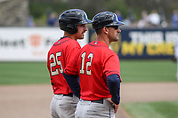 Cedar Rapids Kernels first baseman Edouard Julien (25) and manager Brian Dinkelman (12) look on from third base during a game against the Wisconsin Timber Rattlers on September 8, 2021 at Neuroscience Group Field at Fox Cities Stadium in Grand Chute, Wisconsin.  (Brad Krause/Four Seam Images)