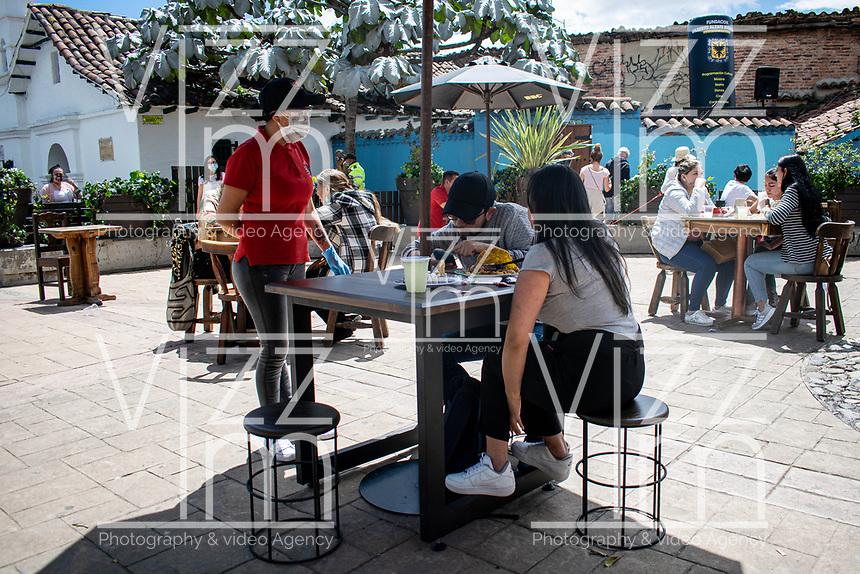 """BOGOTA - COLOMBIA, 05-09-2020: Una mesera atiende a los comensles durante el primer día del piloto de apertura de restaurantes y cafés al aire libre, denominado """"Bogotá a Cielo Abierto"""", en el Chorro de Quevedo en el centro de Bogotá que ahora tiene sus calles pintadas con formas geométricas en pintura neón y cuenta con mesas, distribuidas estratégicamente para mantener el distanciamiento físico al finalizar la cuarentena total en el territorio colombiano causada por la pandemia  del Coronavirus, COVID-19. / A waitress serves the diners during the first day of the pilot for the opening of restaurants and outdoor cafes, called """"Bogotá a Cielo Abierto"""", in Chorro de Quevedo in the center of Bogotá, which now has its streets painted with geometric shapes in neon paint and has tables, strategically distributed to maintain physical distancing at the end of the total quarantine in the Colombian territory caused by the Coronavirus pandemic, COVID-19. Photo: VizzorImage / Johan Rugeles / Cont"""