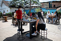 "BOGOTA - COLOMBIA, 05-09-2020: Una mesera atiende a los comensles durante el primer día del piloto de apertura de restaurantes y cafés al aire libre, denominado ""Bogotá a Cielo Abierto"", en el Chorro de Quevedo en el centro de Bogotá que ahora tiene sus calles pintadas con formas geométricas en pintura neón y cuenta con mesas, distribuidas estratégicamente para mantener el distanciamiento físico al finalizar la cuarentena total en el territorio colombiano causada por la pandemia  del Coronavirus, COVID-19. / A waitress serves the diners during the first day of the pilot for the opening of restaurants and outdoor cafes, called ""Bogotá a Cielo Abierto"", in Chorro de Quevedo in the center of Bogotá, which now has its streets painted with geometric shapes in neon paint and has tables, strategically distributed to maintain physical distancing at the end of the total quarantine in the Colombian territory caused by the Coronavirus pandemic, COVID-19. Photo: VizzorImage / Johan Rugeles / Cont"