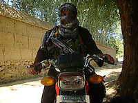 A sub-commander from the Wardak Mobile Patrol Unit sit on a chinese motorcycle before he goes out on patrol armed with an AK47 machine gun