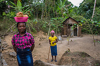 "Haiti, Gros-Morne. Christella Sigene Mercy Beyond Borders scholar and Constella, her mother, at their home. Sweeping in front of their kitchen. ""With an education my daughter can have a better life, she can be a doctor or an engineer."""