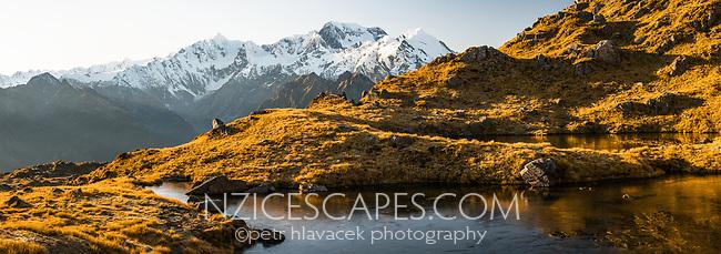 Sunrise over alpine tarn with Southern Alps and its main highest peaks Aoraki Mount Cook, Mount Tasman and La Perouse, Westland Tai Poutini National Park, UNESCO World Heritage Area, West Coast, New Zealand, NZ