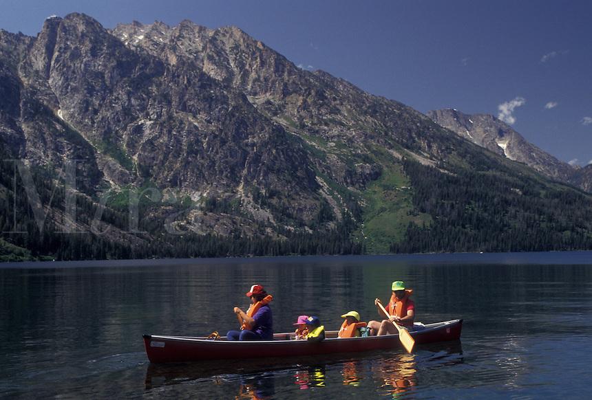 AJ3578, canoe, Grand Teton National Park, Lake Jenny, Grand Teton, Wyoming, Grand Teton Mountain, Rocky Mountains, A family paddles their canoe on Lake Jenny with a view of the majestic Teton Mountains behind in Grand Teton National Park in the state of Wyoming.
