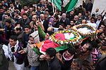 Palestinian carry the body of Jawaher Abu Rahmah during her funeral at the her West Bank Village of Bil'in, on 01 January 2011. Jawaher, 36, who was protesting against Israel's West Bank separation barrier, was evacuated to the Ramallah hospital on 31 December 2010 after inhaling massive amounts of tear-gas during the weekly Friday protest in Bilin, and died on 01 January 2011 morning after she did not respond to medical treatment. Abu Rahmah was the sister of Bassem Abu Rahmah, who was killed during a protest in the same village, which is located about four kilometres from the Israel-West Bank border on 17 April 2009. Photo by Issam Rimawi