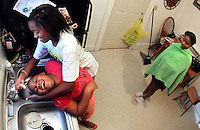 Markeshia Kennedy, 16, washes the hair of her sister, Jasmine, 9, while sister DeJoan towels off following her washing in their Des Moines home.  The sisters were working on their hair together in preparation for the first day of school.  The girls along with their mother, Stephanie Kennedy, have settled in Des Moines after their home was flooded by Hurricane Katrina in 2005.