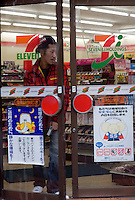 A young man walks out from a 7-Eleven convenience store in Tokyo, Japan. 7-Eleven is part of an international chain of convenience stores, operating under Seven-Eleven Japan Co. Ltd, which in turn is owned by Seven & I Holdings Co. of Japan..