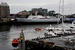 View of Victoria, British Columbia, inner harbor with tourists leaving on whale watching boats and the ferry Coho lying at the dock.