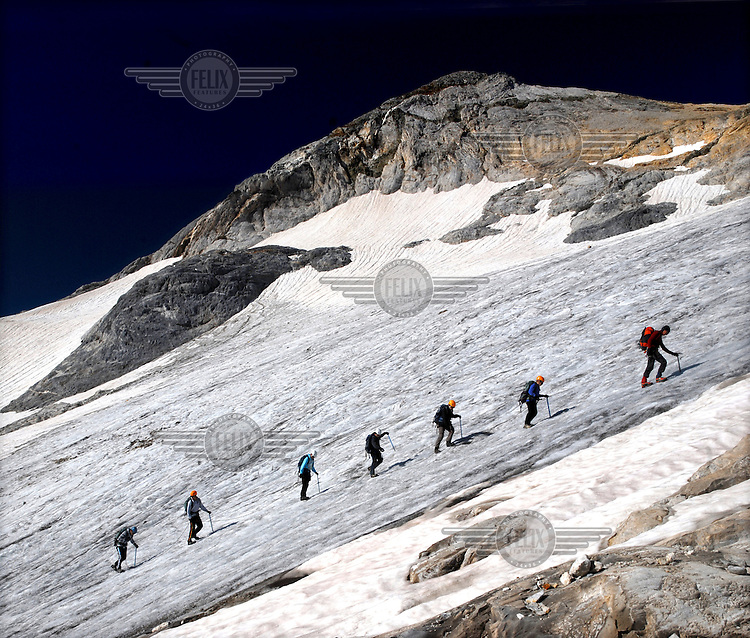 A group of mountain climbers, roped together, as they ascend to the summit of Vignemale (3299m) through Glacier d'Ossoue, the largest in the French Pyrenees.