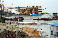 Children play near a shipyard on the shores of Dongting Lake, Hunan Province. Dongting Lake has decreased in size in recent decades as a result of land reclamation and damming of the Yangtze. China. 2010