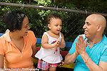 14 month old toddler girl outside at playground with parents language development clapping hands and singing song