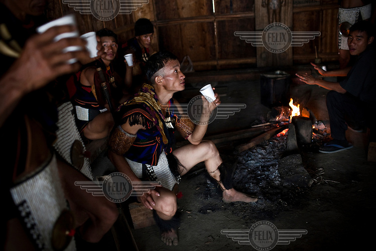 Warriors from the Khiamniungan in their traditional attire relax in their Morang (Bachelor house) at the Hornbill Festival, where the state's sixteen tribes display their traditional ceremonial dress, dances and cuisine.