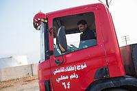 Feuerwehr in Qamishli, Rojava/Syrien.<br /> Von sieben Feuerwehr-Fahrzeugen die der YPG-Regierung in Qamishli zur Verfuegung stehen, ist nur eines funktionstuechtigt. Fuenf Fahrzeuge sind mit vorhandenen Mitteln nicht zu reparieren - Motorschaden, unbenutzbare Fahrerkabinen, defekte Stromleitungen.<br /> Zusaetzlich zumden Augaben der Feuerwehr muessen die 12 Feuerwehrmaenner - je 3 von ihnen arbeiten in 24-Stundenschichten - auch noch Wasser in Stadtteile ohne Wasserversorgung verteilen.<br /> Im Bild: Der arabische Feuerwehrmann Aziz rueckt mit einem Kollegen zur Wasserverteilung aus.<br /> 15.12.2014, Qamishli/Rojava/Syrien<br /> Copyright: Christian-Ditsch.de<br /> [Inhaltsveraendernde Manipulation des Fotos nur nach ausdruecklicher Genehmigung des Fotografen. Vereinbarungen ueber Abtretung von Persoenlichkeitsrechten/Model Release der abgebildeten Person/Personen liegen nicht vor. NO MODEL RELEASE! Nur fuer Redaktionelle Zwecke. Don't publish without copyright Christian-Ditsch.de, Veroeffentlichung nur mit Fotografennennung, sowie gegen Honorar, MwSt. und Beleg. Konto: I N G - D i B a, IBAN DE58500105175400192269, BIC INGDDEFFXXX, Kontakt: post@christian-ditsch.de<br /> Bei der Bearbeitung der Dateiinformationen darf die Urheberkennzeichnung in den EXIF- und  IPTC-Daten nicht entfernt werden, diese sind in digitalen Medien nach §95c UrhG rechtlich geschuetzt. Der Urhebervermerk wird gemaess §13 UrhG verlangt.]