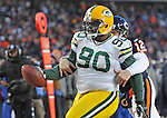 Green Bay Packers nose tackle B.J. Raji scores a touchdown after intercepting Bears quarterback Caleb Hanie (12), attempting to tackle Raji, against the Chicago Bears during the fourth quarter of the NFC Championship game at Soldier Field in Chicago, Ill., on Sunday, Jan. 23, 2011.