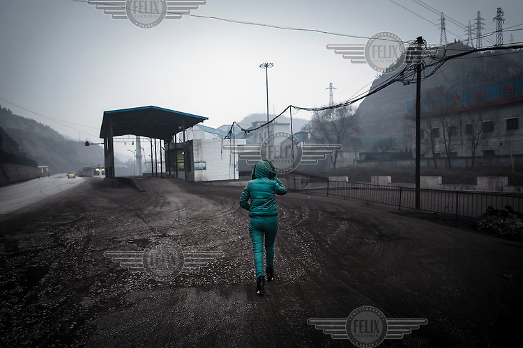 A woman walks towards the Xinwu Coal Mine which is owned by Liansheng Group, a coal mining company that has been hit by the falling price of the fossil fuel leaving the firm struggling to repay its loans.