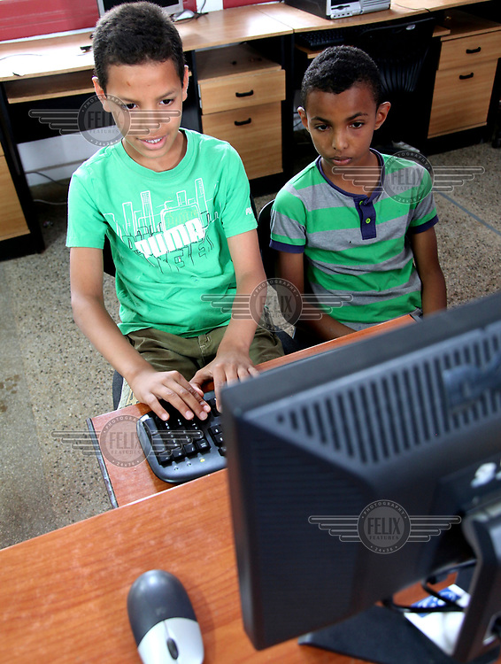 Two boys use a computer at the 'Akkari' centre, a home for abandoned children and orphans. The centre offers a shelter to 225 boys from 5 to 18 years old.