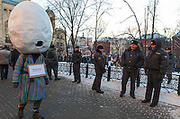 Moscow, Russia, 15/12/2012..A man wearing an egg for a head and signs reading ?The Eggman is just walking? and ?The Eggman does not go to unauthorised rallies? walks past police in Lubyanka Square at an unauthorised opposition rally to mark a year of protests against Vladimir Putin.