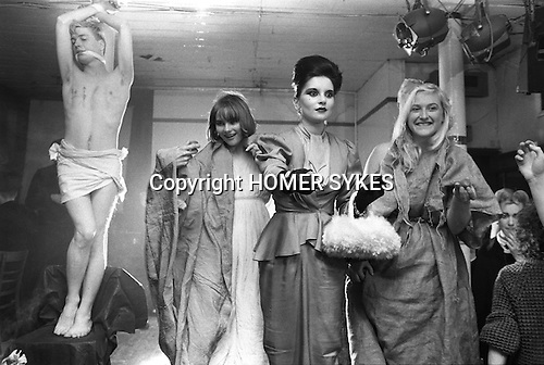 """Blitz Kids New Romantics at The Blitz Club Covent Garden, London, England 1980. At the Easter Pageant,  Princess Julia (centre ) handing out Cadburys Creme chocolate Easter eggs to the crowd. They had just performed the song, Death Where is Thy Sting?  [L-R] Iain R Webb [fashion author, editor journalist],  Princess Julia, Jennifer Binnie,  and sister Christine """"Miss Binnie""""<br /> <br /> """"Instead of 'RIP' Princess Julia scrawled 'HIP' on my chest in lipstick, """" writes Iain R Webb."""