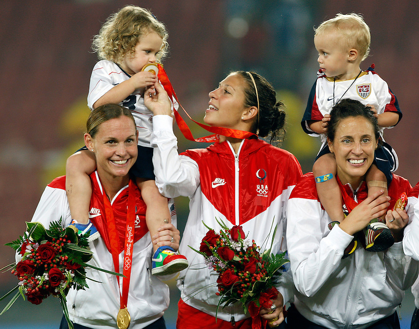 BEIJING --Kylie Rampone, 3, on her mom Christie Rampone's shoulders, kisses the gold medal of Carli Lloyd (center) as Keegan Markgraf, 2, with his mom Kate Markgraf  look on atop the medal platform as the United States celebrates its win over Brazil in the gold medal women's soccer game at Workers' Stadium at of the Beijing 2008 Olympic Games. The Rampone family is from Manasquan, N.J. and Lloyd, who scored the game's only goal is from Delran, N.J.  (8/21/08)  ANDREW MILLS/THE STAR-LEDGER..