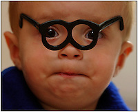 A young boy hams it up while playing with a small pair of glasses (from a Mr. Potatohead game). Image is model released.