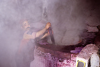 Tunisian Hat, Chechia.  Steam Surrounds Worker Stirring Vat of Boiling Dye in Chechia Workshop.