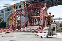 Stop lights and gates move into position before the Center Street Swing Bridge swings into position to allow a tanker to pass on the Cuyahoga River in Cleveland, Ohio.  The bridge carries vehicular traffic over the river from underneath the Veterans Memorial Bridge.
