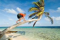 Man in orange shirt and green shorts playing around on tropical island beach, Comarca De Kuna Yala, San Blas Islands, Panama