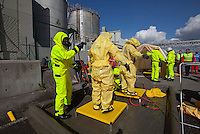 Paramedics in HAZMAT suits gets hosed down and cleaned before undressing at the other side. HarbourEx15, a field training exercise with scenarios connected to operations in the harbor April 27th – 29th 2015.<br />