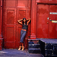 African American girl standing in front of burgandy colored building<br />