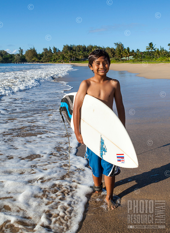 A grinning young local boy with his surfboard at Hanalei Beach, Kaua'i.
