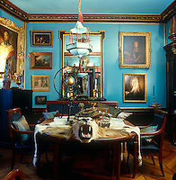 """The electric """"Cotton Blue"""" of the walls and gilt-framed paintings have created a jewel-box feel to the library of this Empire-style Parisian apartment"""