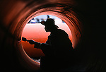 man painting inside of huge pipe, working at Fengjie, a city in the Three Gorges, Cina, Asia