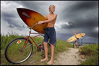 Anthony Williams, 14, and his sister Cassandra High, 17, have a sense of urgency and concern as they leave the beach with their surfboards as a heavy storm approaches Ormond-By-The-Sea.
