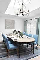The formal dining room in the extension is lit from above by a skylight during the day and a chandelier in the evening