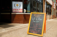 A sign outside of Industry Public House on Butler Street is shown letting patrons know their doors are still open for takeout on Friday March 20, 2020 in the Lawrenceville neighborhood of Pittsburgh, Pennsylvania. (Photo by Jared Wickerham/Pittsburgh City Paper)