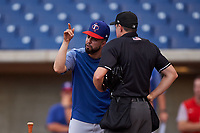 AZL Rangers manager Carlos Cardoza (65) argues with home plate umpire Tyler Wall during an Arizona League game against the AZL Brewers Blue on July 11, 2019 at American Family Fields of Phoenix in Phoenix, Arizona. The AZL Rangers defeated the AZL Brewers Blue 5-2. (Zachary Lucy/Four Seam Images)