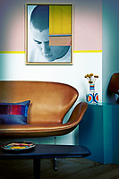 A low coffee table is placed in front of a brown leather Arne Jacobsen Swan seat. The wall behind is painted in a graphic style with a combination of colours: pink, white, grey with a yellow contrasting border.