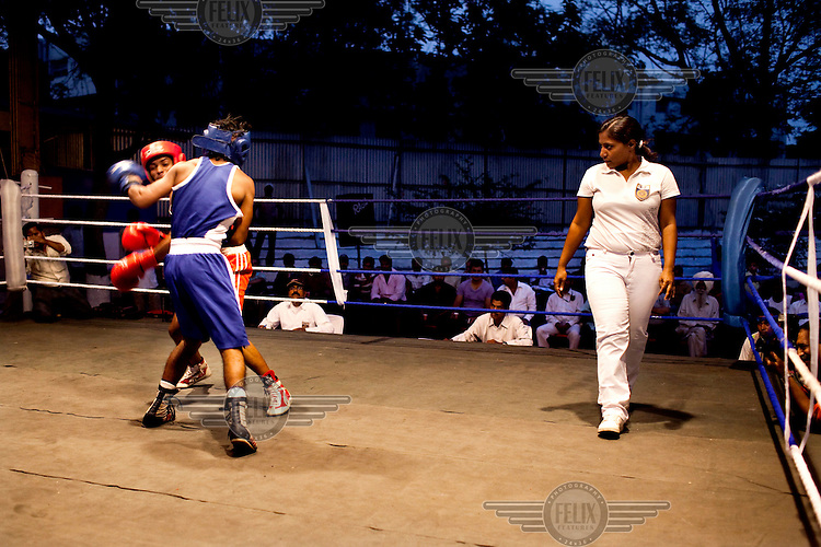 Razia Shabnam referees a bout at an all-India invitational boxing competition in Burnpur. Razia Shabnam was one of the first women boxers in Kolkata and also the first woman in her community to go to college. She is now a coach and one of only three international female boxing referees in India.