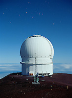 Canada-France-Hawaii Telescope in moonlight.  Moonlight has a similar color to daylight, because the moon reflects sunlight.  Stars, including Polaris, can be seen in the sky above the telescope.  Mauna Kea, Hawaii.