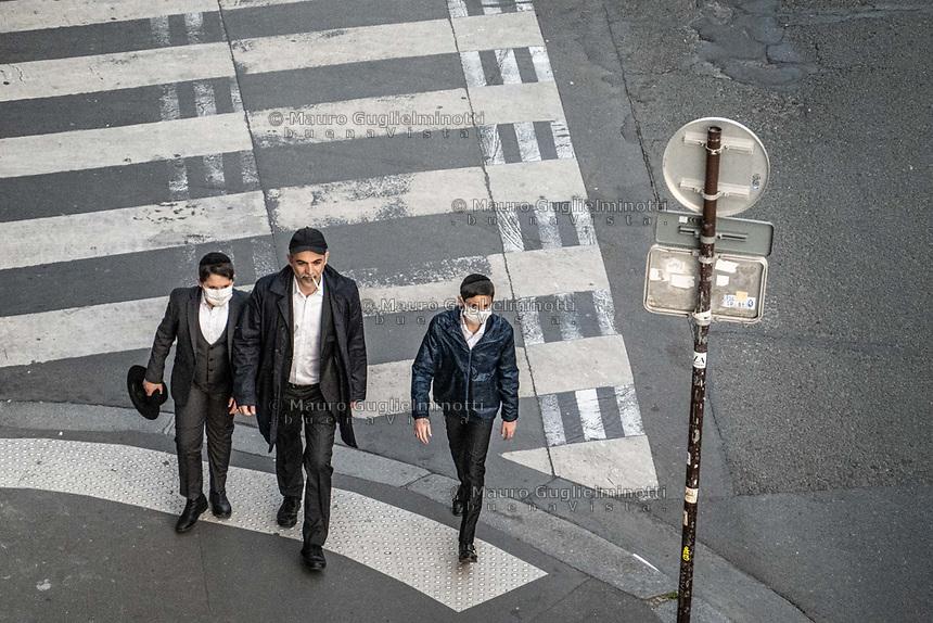 Padre e due figli ebrei passeggiano , con mascherin eprotettive , durante il lockdown a Parigi