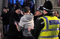 Pictured: A policeman breaks off people fighting in the early hours of New Year's Day. Sunday 01 January 2017<br />Re: Revellers out celebrating the New Year in the pub and club on Wind Street Swansea