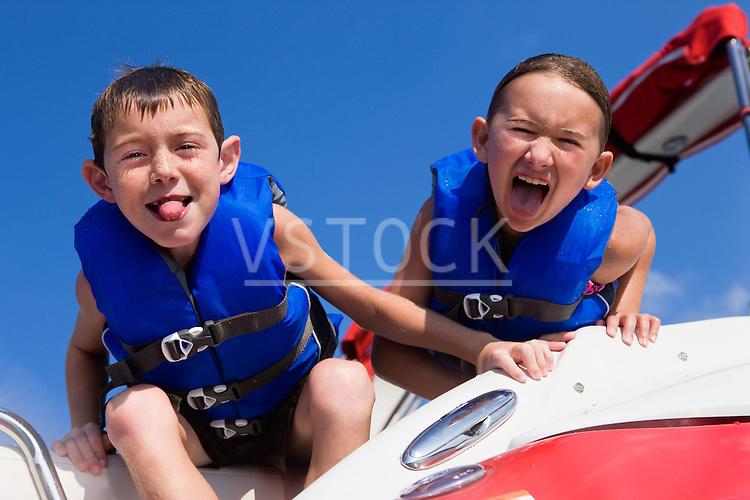 USA, Missouri, Stockton, Stockton Lake, boy (6-7) and girl (8-9) on boat making faces
