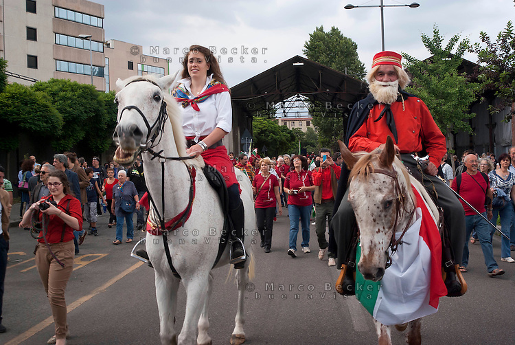 "Sesto San Giovanni (Milano), iniziativa di Radiopopolare per celebrare i 150 anni dell'unità d'Italia: 1000 cittadini italiani di origine straniera indossano una maglietta rossa e sfilando in corteo impersonano i ""nuovi garibaldini"". Le figure di Anita e Giuseppe Garibaldi a cavallo guidano il corteo  --- Sesto San Giovanni (Milan), independent Radio station Radiopopolare initiative to celebrate the 150th anniversary of the unification of Italy: 1000 Italian citizens of foreign origin wear a red shirt and march in procession embodying the ""new follower of Garibaldi"". The figures of Anita and Giuseppe Garibaldi on their horses leading the parade"