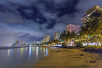 A woman enjoys sitting at Kuhi'o Beach under a cloudy night sky, with lights from surrounding hotels reflecting off the water, Waikiki, O'ahu.